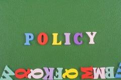 在从五颜六色的abc字母表块木信件组成的绿色背景,广告文本的拷贝空间的政策词 库存图片