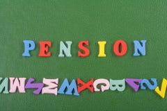 在从五颜六色的abc字母表块木信件组成的绿色背景,广告文本的拷贝空间的退休金词 库存照片