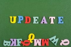 在从五颜六色的abc字母表块木信件组成的绿色背景,广告文本的拷贝空间的UPDEATE词 免版税库存图片