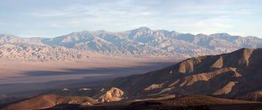 在死亡谷的看法与干盐湖的日落在背景的光和山的 免版税库存图片