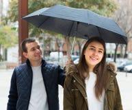 在年轻人之下的夫妇伞 免版税库存照片