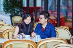 在巴黎人咖啡馆的年轻浪漫亚洲夫妇 免版税库存照片