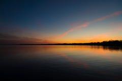 在令人毛骨悚然的湖的日落天空 免版税库存图片