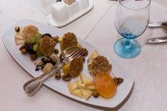 在宴会桌上的开胃食物:葡萄,乳酪,坚果,快餐 蓝色葡萄酒杯 免版税库存照片