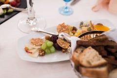 在宴会桌上的开胃食物:葡萄,乳酪,坚果,快餐 免版税库存照片