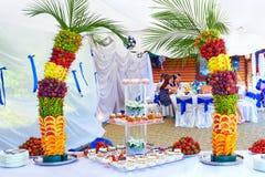 在宴会的五颜六色的果子和蛋糕装饰集会 免版税库存图片
