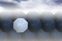 在黑伞中的白色伞 免版税库存照片