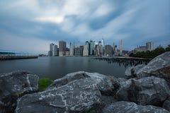在更低的曼哈顿地平线视图的多云天从布鲁克林大桥 免版税库存照片