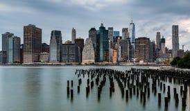 在更低的曼哈顿地平线视图的多云天从布鲁克林大桥 库存照片