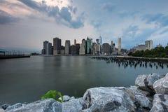 在更低的曼哈顿地平线视图的多云天从布鲁克林大桥 库存图片