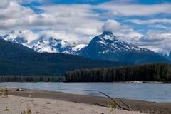 在更低的Stikine河,不列颠哥伦比亚省,加拿大含沙河岸的积雪覆盖的峰顶  免版税库存照片