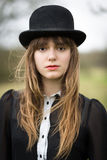 在黑佩带的圆顶硬礼帽打扮的美丽的少妇 免版税库存照片