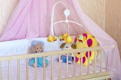 在轻便小床的各种各样的软的玩具有橙色亚麻布的 库存照片