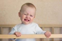 在轻便小床的婴孩啼声 库存图片