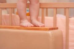 在轻便小床附近的小儿童腿 免版税库存图片
