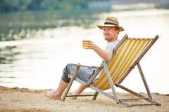 在轻便折叠躺椅的人饮用的啤酒 图库摄影