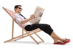 在轻便折叠躺椅的商人读报纸的 免版税库存图片
