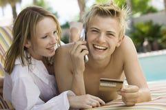 在轻便折叠躺椅的年轻夫妇由水池供以人员做信用卡购买在手机画象 库存照片