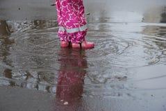 在从儿童` s脚的水坑飞溅并且盘旋 一个小女孩的腿在水坑到处乱跑  免版税库存照片