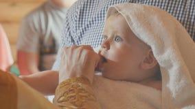 在婴儿洗礼期间,教士做仪式涂油与油 股票视频
