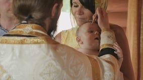 在婴儿洗礼期间,教士做仪式涂油与油 股票录像