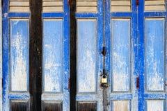 在经典中葡萄牙建筑风格shophouse大厦的老土气蓝色木折叠门的背景纹理 免版税库存照片