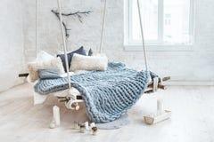 在经典斯堪的纳维亚样式的白色顶楼内部 从天花板暂停的垂悬的床 舒适大被折叠的灰色格子花呢披肩 免版税库存图片