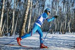 在经典样式的侧视图年轻滑雪者运动员冬天桦树森林短跑种族 库存照片