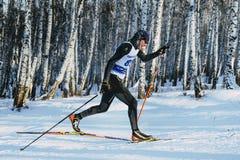 在经典样式的侧视图年轻滑雪者运动员短跑种族 免版税库存图片