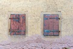 在经典plae的两个木质的窗口在欧洲染黄老墙壁 库存照片