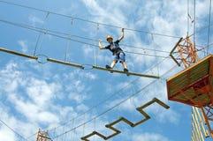 在绳索冒险公园一年轻人平衡 库存照片