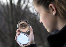 在紧凑镜子的女孩的眼睛 库存照片