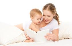 在去前睡照顾阅读书婴孩在床上 免版税库存图片