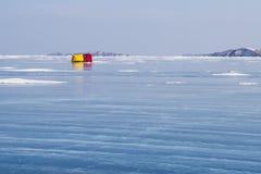 在贝加尔湖冰的红色和黄色帐篷在山背景的冬天 库存图片