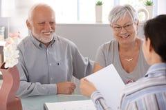 在财务顾问微笑的高级夫妇 库存图片