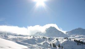 在滚动在一座多雪的山的云彩的阳光 免版税图库摄影