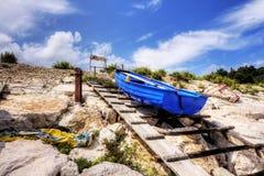 在滑动式造船架的蓝色小船 库存图片