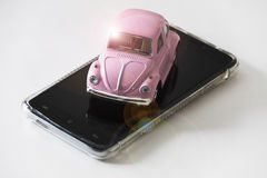 在移动电话的桃红色玩具汽车 库存照片