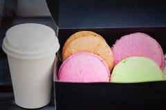 在黑匣子和一个杯子的法国五颜六色的蛋白杏仁饼干热的饮料 图库摄影