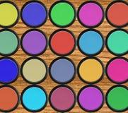 在黑匣子的五颜六色的眼影膏在木桌 库存照片