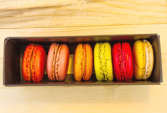 在黑匣子的五颜六色的macarons在木背景 库存图片