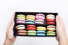 在黑匣子的鲜美不同的色的macarons在白色backgroundn 免版税图库摄影