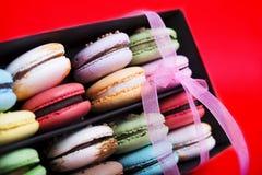 在黑匣子的鲜美不同的色的macarons在红色背景 免版税库存图片