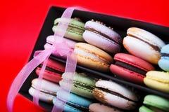在黑匣子的鲜美不同的色的macarons在红色背景 库存照片