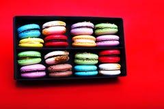 在黑匣子的鲜美不同的色的macarons在红色backgroundn 免版税库存照片