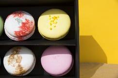 在黑匣子的鲜美不同的色的macarons在黄色背景 免版税库存照片