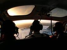 在从直升机后座和2位乘客里面采取的直升机、飞行员  免版税库存照片
