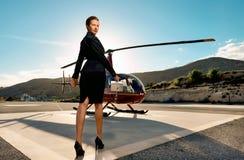 在直升机附近的典雅的女商人 免版税图库摄影