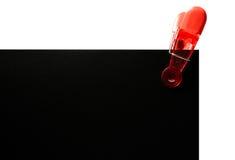 在黑卡片的红色纸夹 免版税库存图片