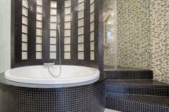 在黑卫生间里面的圆的浴缸 免版税图库摄影